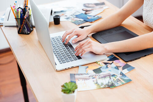 Closeup of hands of young woman typing on laptop keyboard and using graphic tablet