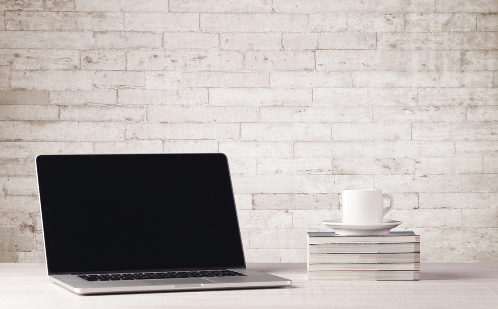 An open laptop on an office desk with flower, coffee, books in front of white brick wall background concept