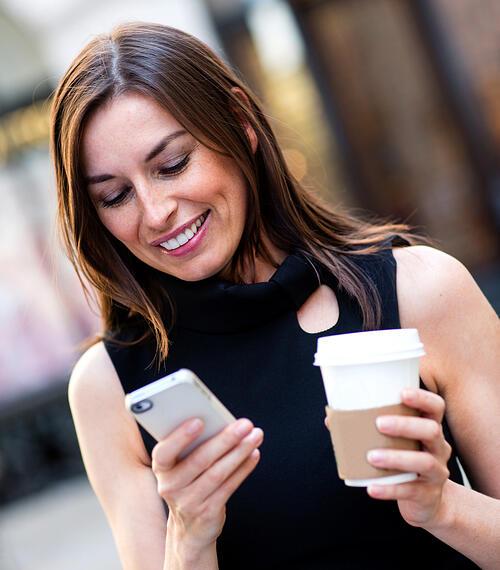 lady holding her iPhone in one hand, coffee in the other