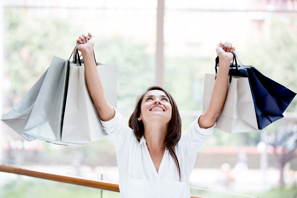 Happy shopping woman with arms up holding bags.jpeg