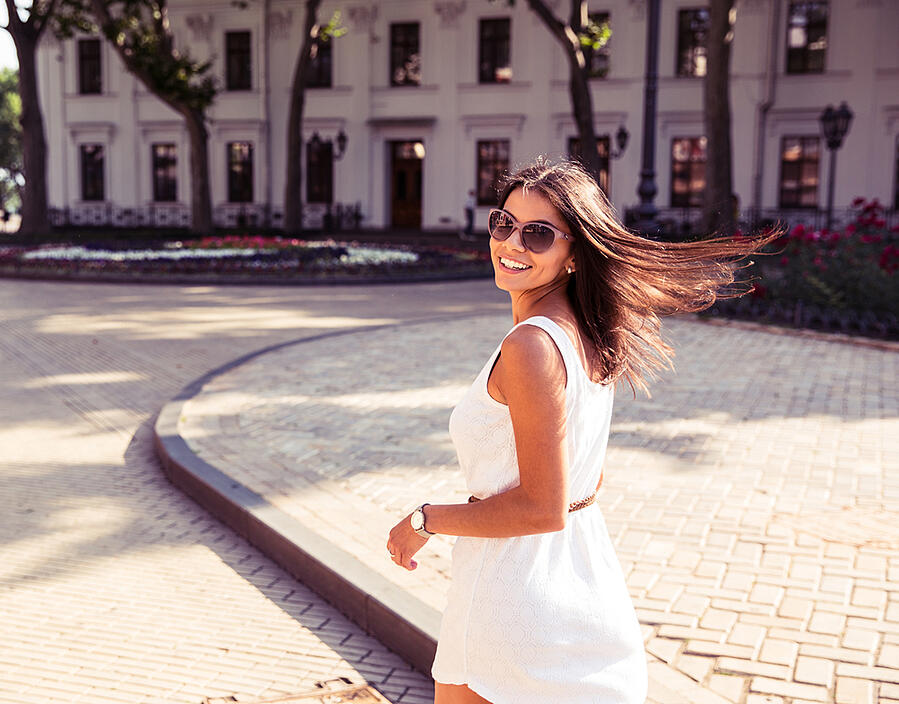 Happy woman in sunglasses and dress walking outdoors. Looking at camera