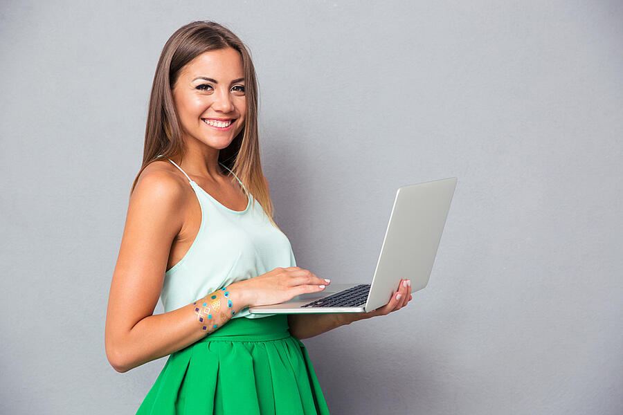 1. lady holding a laptop against a gray wall 2. hand holding a silver pen writing on white paper