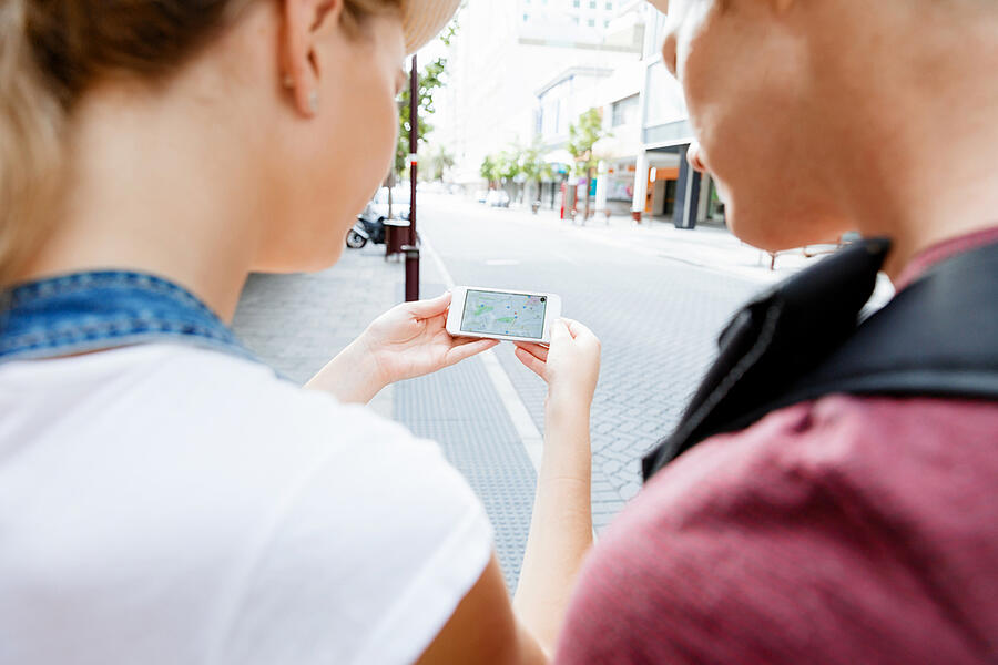 Tourists using navigation app on the mobile phone.
