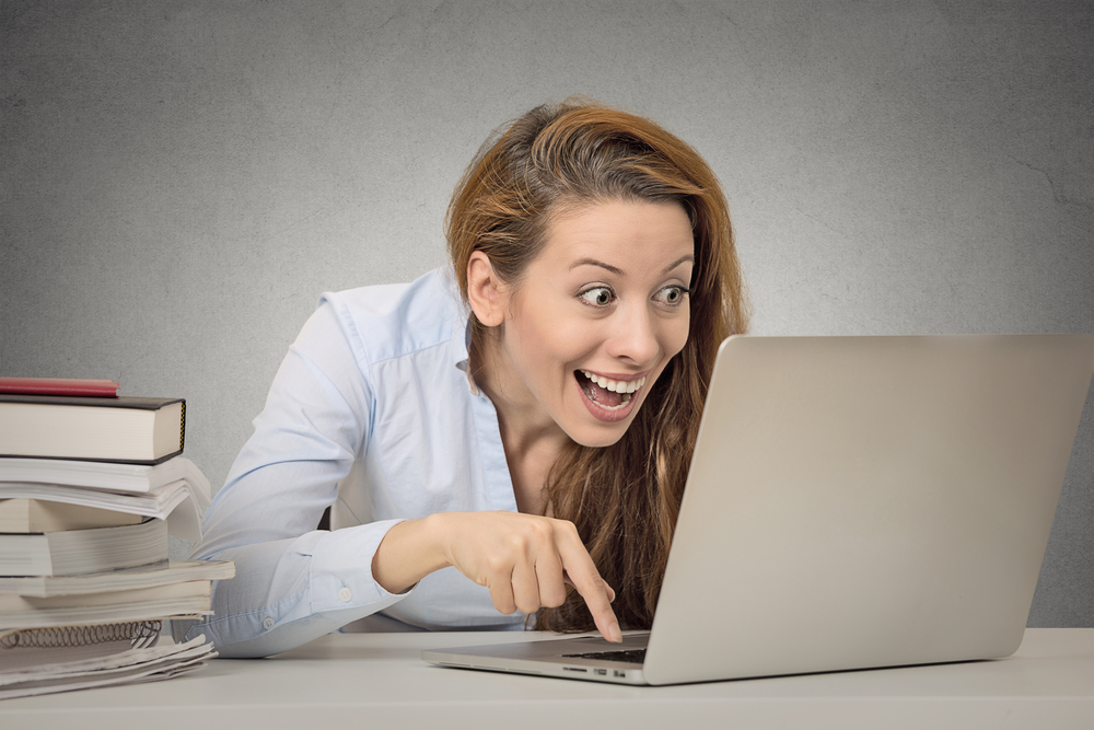 Woman working on computer ready press enter button isolated grey office wall background. Funny funky crazy looking girl excited what she see on laptop screen browsing internet. Face expression emotion