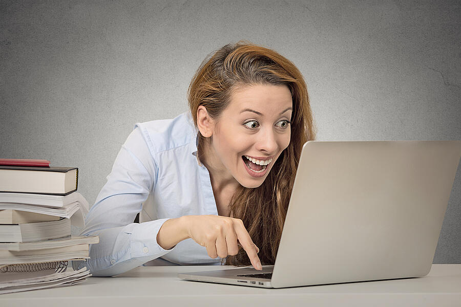 smiling lady with laptop - typing with index finger