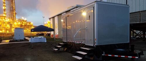 raised, silver trailer in parking lot with steps leading to the doors