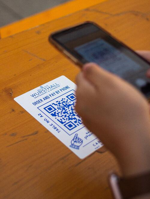 adWhite Resurgence of QR Codes and Why This Matters for your Marketing Image of Phone Scanning QR Code on Restaurant Table