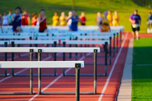 high school track with hurdles and runners