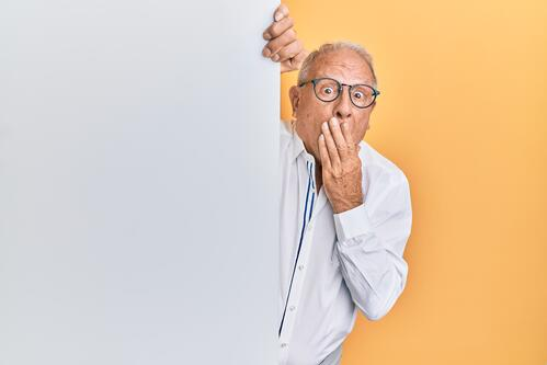 Man peering from behind a white wall with hand over his mouth.